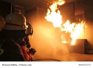 Zwei Feuerwehrleute der Feuerwehr Siegen bei einer Brandbekaempfung in einer Brandsimulationsanlage. Hier wurde ein Zimmerbrand nachgestellt und unter realistischen Bedingungen bekaempft.
